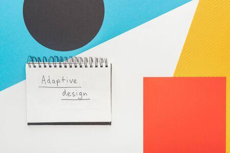 Foto de top view of notebook with adaptive design lettering on abstract geometric background - Imagen libre de derechos