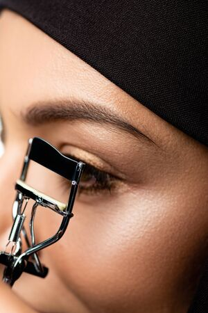 Photo pour close up view of young Muslim woman in hijab using eyelash curler - image libre de droit