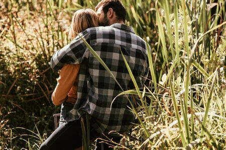 Photo for back view of man in plaid shirt embracing girlfriend in thicket of sedge - Royalty Free Image