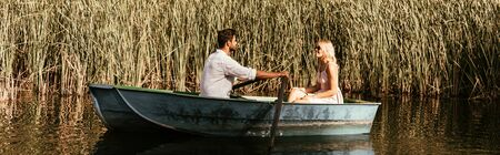 Photo for panoramic shot of young couple in boat on river near thicket of sedge - Royalty Free Image