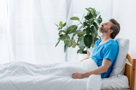Photo for side view of patient in medical gown looking up in hospital - Royalty Free Image