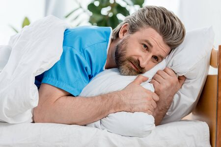 Photo for handsome patient in medical gown lying in bed and looking away - Royalty Free Image