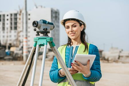 Photo for Surveyor with digital tablet and measuring level smiling at camera - Royalty Free Image