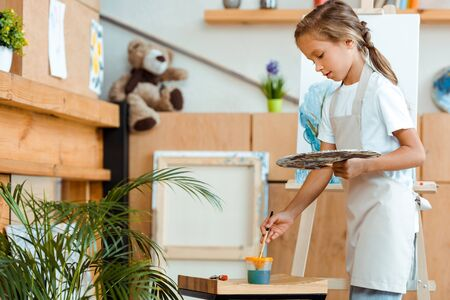 Photo for cute child in apron standing with palette and paintbrush near easel - Royalty Free Image