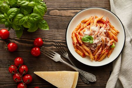 Foto de top view of tasty bolognese pasta with tomato sauce and Parmesan in white plate near ingredients and cutlery on wooden table - Imagen libre de derechos