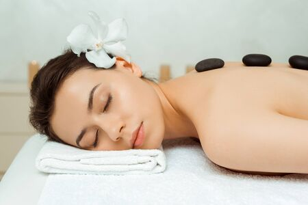 Foto de attractive woman with hot stones on back lying on massage table in spa - Imagen libre de derechos
