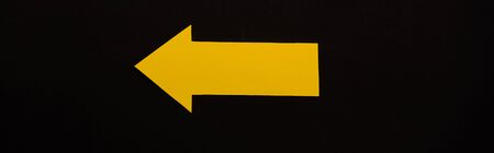 Photo for panoramic shot of yellow directional arrow isolated on black - Royalty Free Image