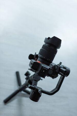 Photo for black digital camera on tripod in studio - Royalty Free Image