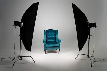Photo for Blue armchair with studio light on grey background - Royalty Free Image