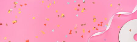 Photo for top view of valentines confetti, empty compact disk, ribbon on pink background, panoramic shot - Royalty Free Image