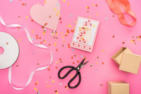 Photo for top view of valentines confetti, empty compact disk, scissors, gift boxes, greeting card on pink background - Royalty Free Image