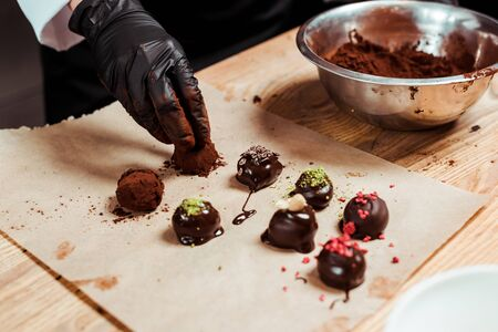 Foto de cropped view of chocolatier in black latex glove preparing truffle candies near chocolate balls - Imagen libre de derechos
