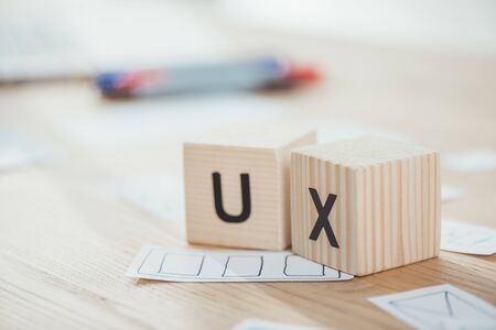 Foto de Selective focus of wooden cubes with ux letters and web sketches on table - Imagen libre de derechos