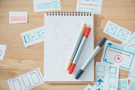 Foto de Top view of pens on notebook with website ux app sketches on wooden table - Imagen libre de derechos