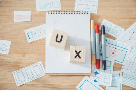 Foto de Top view of cubes with ux letters and website ux app development sketches on wooden table - Imagen libre de derechos