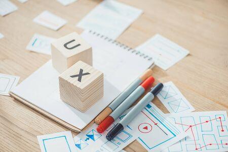 Foto de Selective focus of letters ux on cubes with website app development sketches on wooden table - Imagen libre de derechos