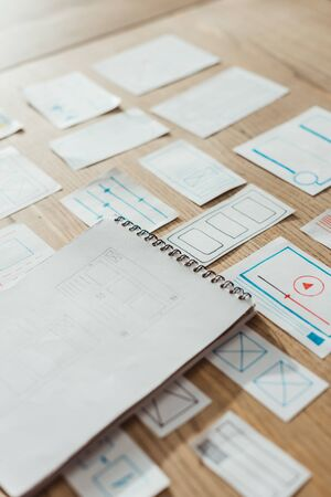 Foto de High angle view of notebook and user experience design sketches on wooden table - Imagen libre de derechos