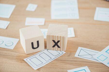Foto de Selective focus of wooden cubes with ux letter and layouts on table - Imagen libre de derechos