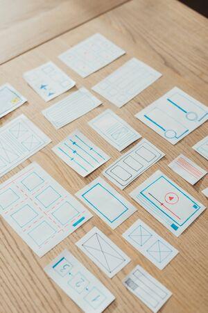 Foto de High angle view of layouts of user experience design on wooden table - Imagen libre de derechos