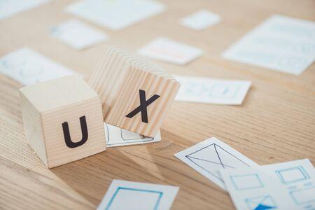 Foto de Selective focus of wooden cubes with ux letters and application layouts on table - Imagen libre de derechos