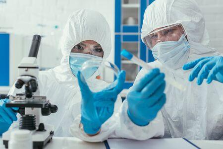Foto de biochemists holding test tube and petri dish near microscope - Imagen libre de derechos