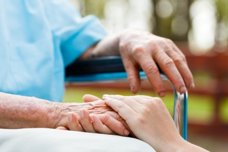 Photo for Doctor holding elderly patient 's hand in a wheelchair.  - Royalty Free Image