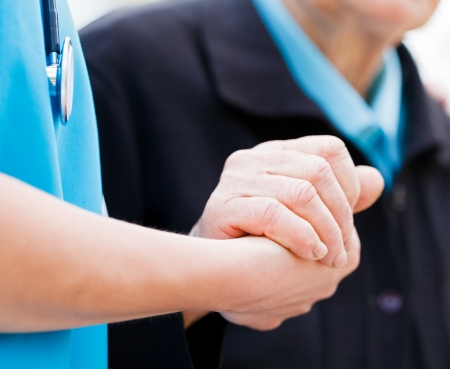 Photo pour Caring nurse or doctor holding elderly lady's hand with care. - image libre de droit