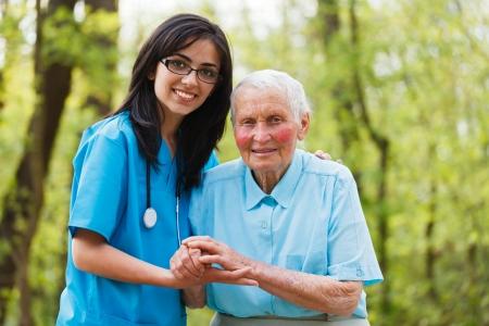 Foto de Kind nurse together with elderly woman in the hospital's garden. - Imagen libre de derechos