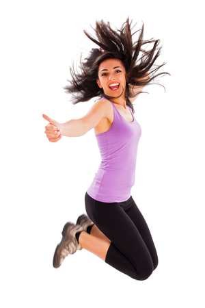 Pretty fit girl showing like sign while jumping high - studio shot.