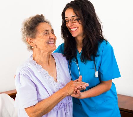 Foto de Happy nurses keeping good mood in nursing home. - Imagen libre de derechos