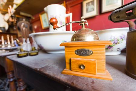 Foto de Old wooden dusty cofee grinder on a wooden table in an antique shop. - Imagen libre de derechos