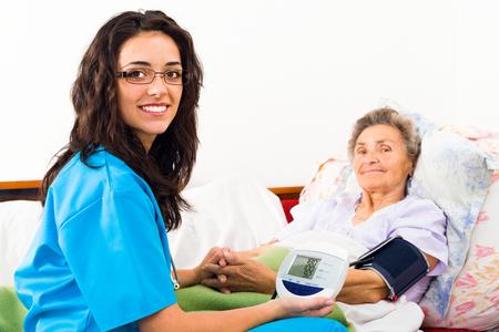 Foto de Kind nurse measuring elderly patient's blood pressure at home. - Imagen libre de derechos