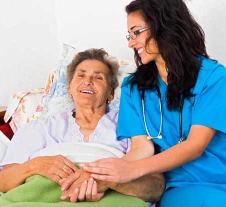 Foto de Kind nurse easing elderly lady's days in nursing home with care help and joy. - Imagen libre de derechos