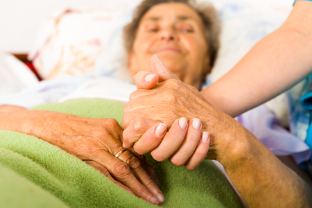 Foto de Health care nurse holding elderly lady's hand with caring attitude. - Imagen libre de derechos