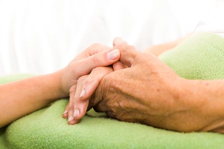 Foto de Health care nurse caring for elderly concept - holding hands. - Imagen libre de derechos