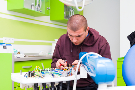 Photo pour Medical equipment engeneer fixing a dental chair in the office of the dentist. - image libre de droit