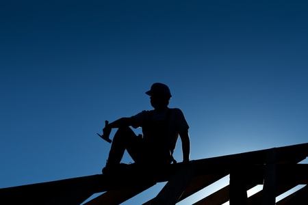 Photo for Builder or carpenter resting on top of roof structure - silhouette with strong back light - Royalty Free Image