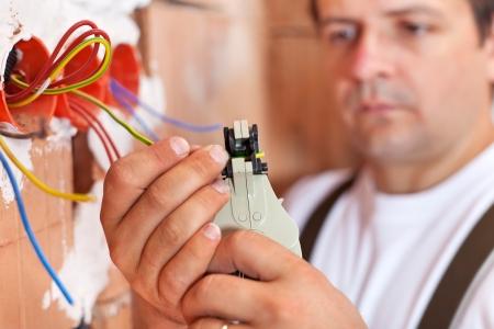 Photo pour Electrician installing electric wires in a new building - closeup on hands - image libre de droit