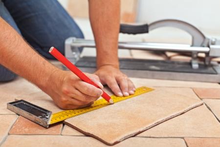 Photo pour Laying ceramic floor tiles - man hands marking tile to be cut, closeup - image libre de droit