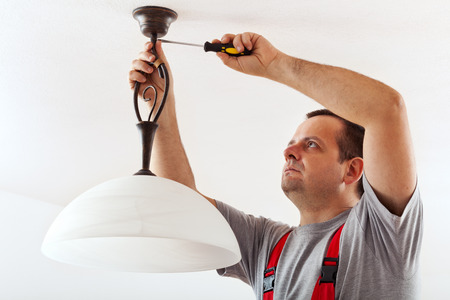 Photo for Electrician mounting ceiling lamp - installing the wires mask - Royalty Free Image
