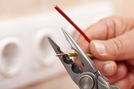 Foto de Pliers peeling copper wires - closeup on electrician hands, wall sockets in the background - Imagen libre de derechos