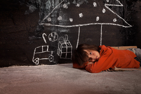 Foto de Poor kid on the street thinking of Christmas gifts - laying on the ground - Imagen libre de derechos