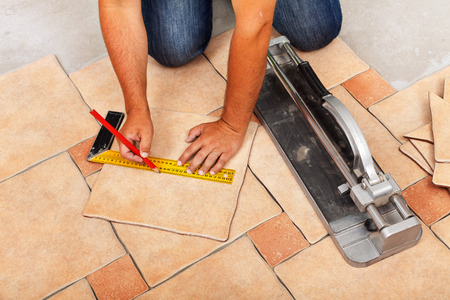 Photo pour Installing ceramic floor tiles - measuring and cutting the pieces, closeup - image libre de droit