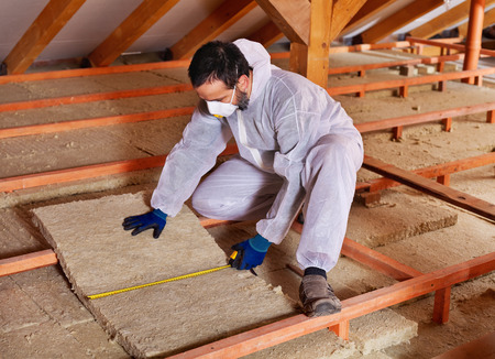 Foto de Man laying thermal insulation layer under the roof - measuring a mineral wool panel - Imagen libre de derechos