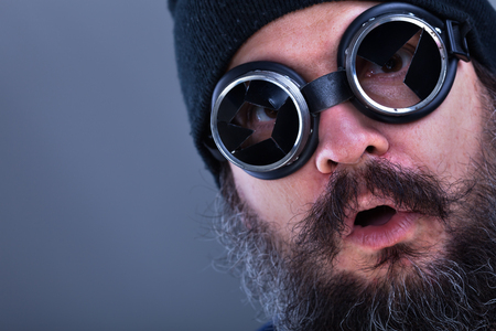 Photo for Strange beard man viewing explosive situation or offer looking surprised with broken welding glasses - closeup, copy space - Royalty Free Image