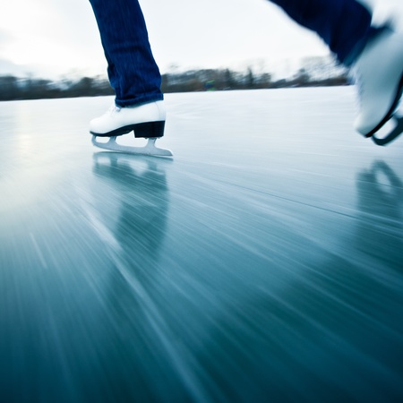 Young woman ice skating outdoors on a pond on a freezing winter day - detail of the legs (motion blur is used to convey speed)