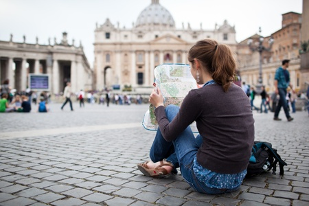 Foto de Pretty young female tourist studying a map at St  Peter - Imagen libre de derechos