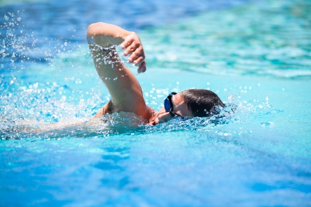 Photo pour Young man swimming the front crawl in a pool - image libre de droit