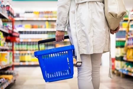 Foto de Pretty young woman buying groceries in a supermarket mall grocery store  color toned image; shallow DOF  - Imagen libre de derechos