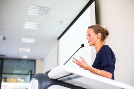 Photo for Pretty young business woman giving a presentation in a conference/meeting setting - Royalty Free Image